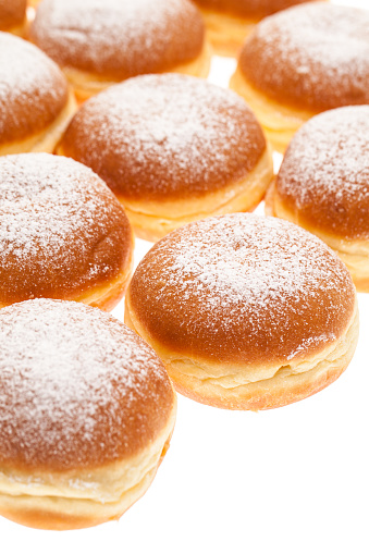 Many Krapfen topped with icing sugar together with empty white space in the lower left corner