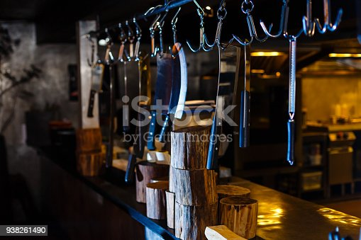 839034546istockphoto Many large knife hanging wooden storage in the kitchen of restaurant 938261490