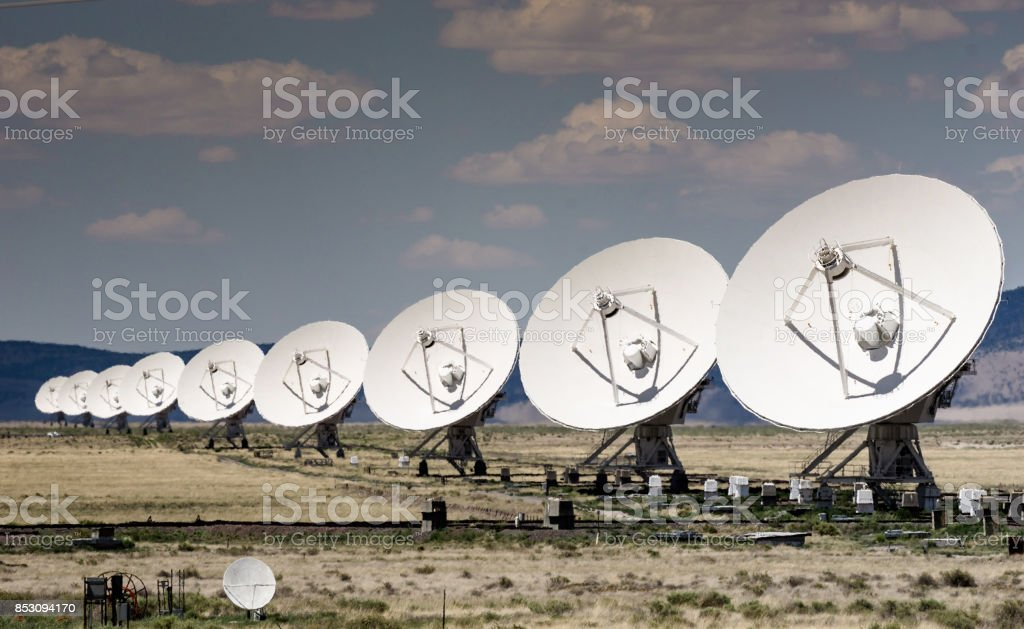 many large satellite dishes all in a row stock photo