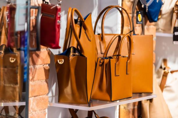 Muitos sacos de couro da bolsa em Siena Italy com a cor marrom alaranjada que pendura no indicador no mercado de rua da compra na cidade - foto de acervo