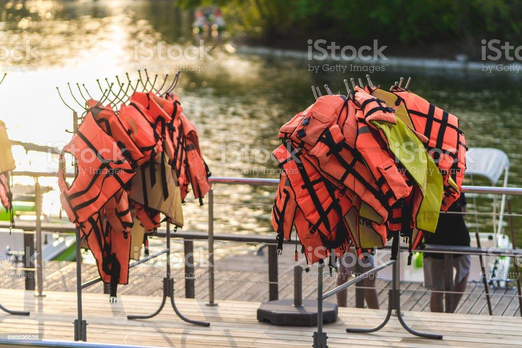 many life vests on the pier. on sunset. stock photo