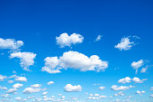 many little fluffy clouds in blue sky in sunny september day