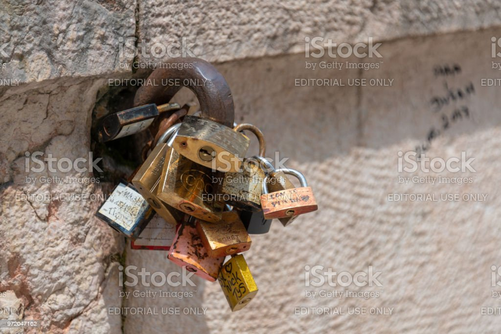 Many Love Locks attached to a metal loop on a wall in Verona, Italy stock photo