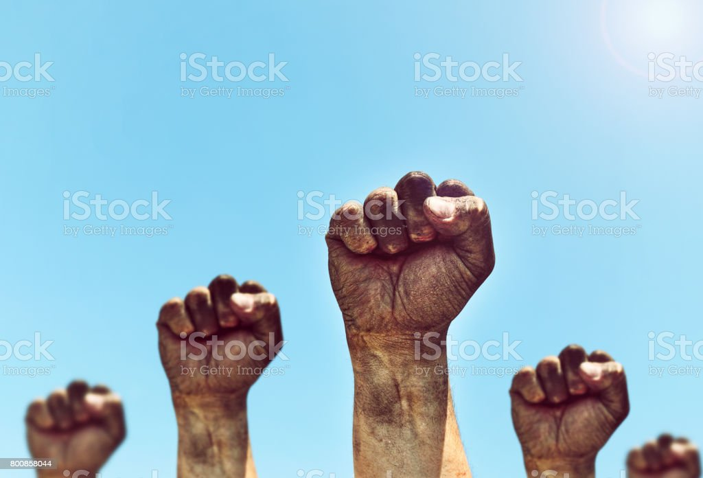 Many male hands are clenched in the fist stock photo