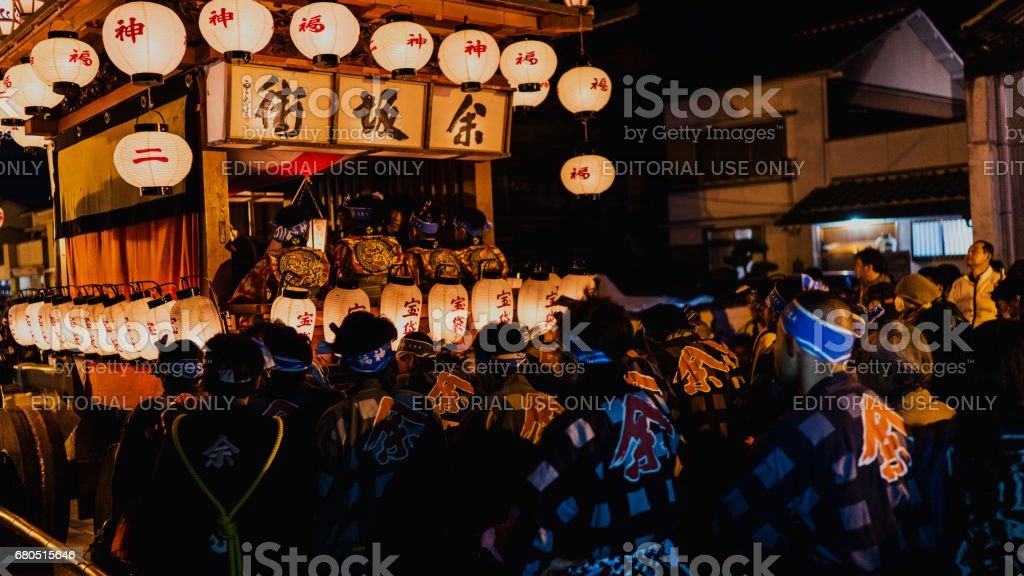 Many men pushing a big float at night stock photo