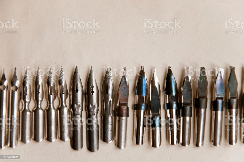 Many metal pens for calligraphy on paper closeup. Top view with empty space. stock photo