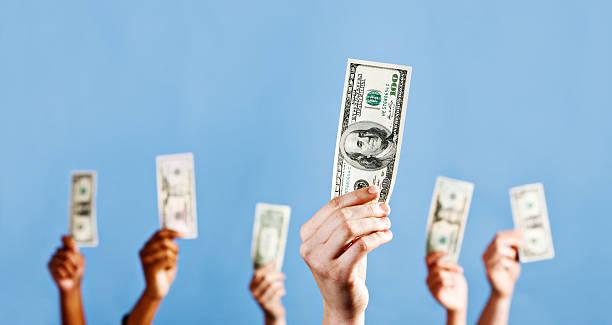 Nombreux mouvements de mains tenir dollars américains contre bleu - Photo