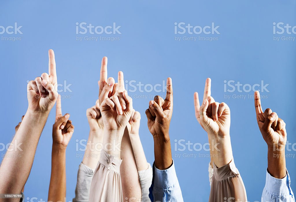 Many mixed hands point upwards into the blue royalty-free stock photo