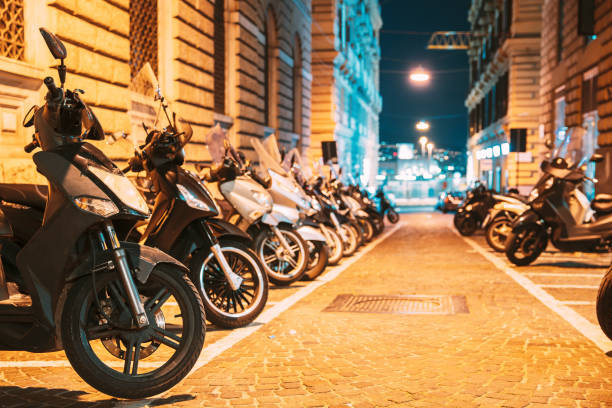 Many Motorbikes, Motorcycles Parked In City. Scooters Parked On Night Street In European City stock photo