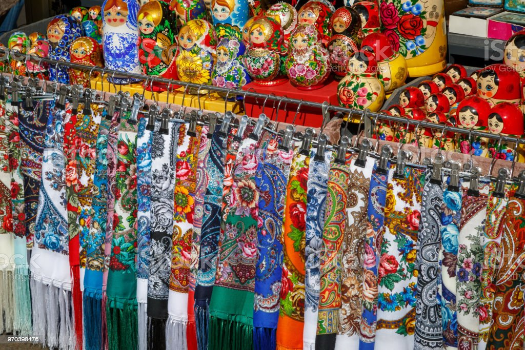 Many Multicolored Fabric Scarves And Painted Dolls