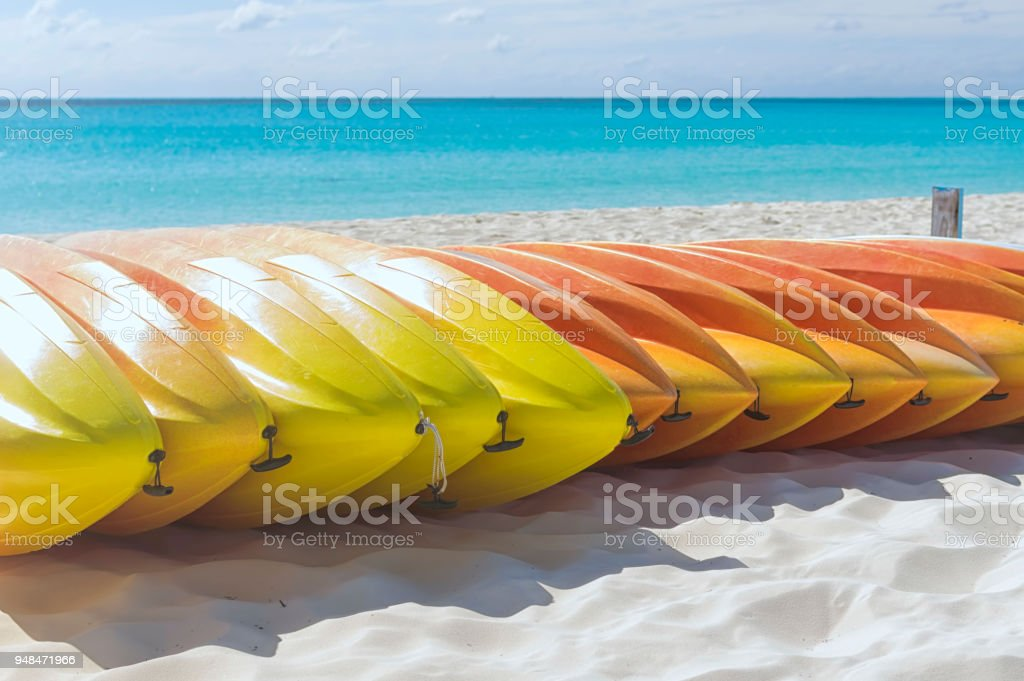 Many multi-colored kayaks lie on the sand against the sea stock photo
