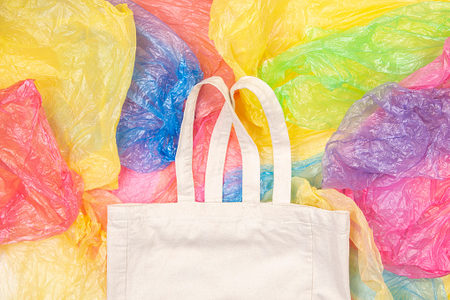 istock Many multicolored plastic bags with one eco natural reusable shopping bag background. Zero waste, eco friendly, sustainability lifestyle, no plastic concept 1131005363
