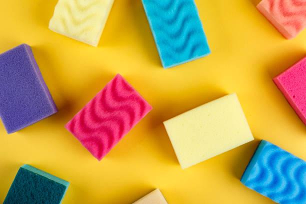 many multicolored sponge for washing dishes on a yellow background. - spugna per le pulizie foto e immagini stock