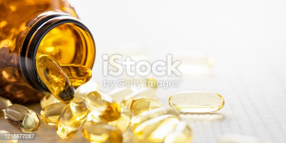 Many nutritional health supplement fish oil capsules spilling out of their bottle onto a white wood table background, shallow depth of focus. Very shallow depth of field with focus being on the rim of the bottle and one isolated capsule on the right of the image. Good copy space.