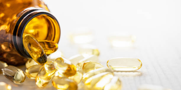 Many nutritional health supplement fish oil capsules spilling out of their bottle onto a white wood table background, shallow depth of focus. stock photo