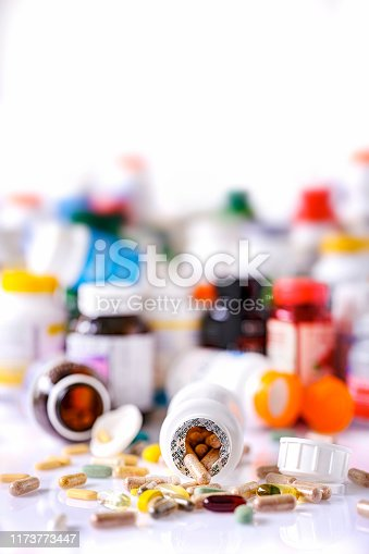 Colorful display and stack of many types of nutritional supplements and vitamin plastic bottles in an out of focus background with many supplement and vitamin capsules and pills in focus in the foreground. Scene set on a white background.