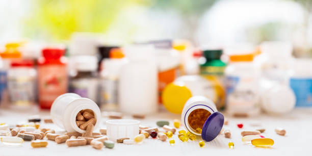 Many nutritional health supplements and vitamins in capsules, tablets on a wood background with their bottles in the background, shallow depth of focus. stock photo