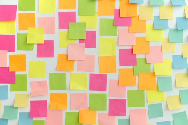 muitos dos adesivos de memória coloridos em um fundo branco. padrão, textura, tema de decoração. dia agitado, conceito de negócios. - post it - fotografias e filmes do acervo