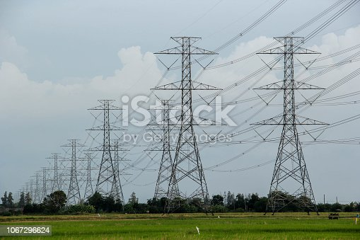 Many of the hight voltage electricity pole stands in a long line on the green rice fields.Power lines were tied together far as the eye can see.