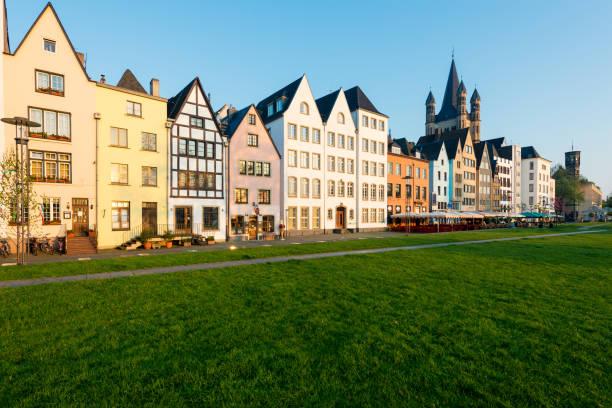 viele von ihnen sind farbenfroh, einen öffentlichen park mit grünem rasen und einige bäume stehen. es gibt ein köln glockenturm auf hintergrund. reisen und architektur-konzepte in deutschland. - restaurant köln stock-fotos und bilder