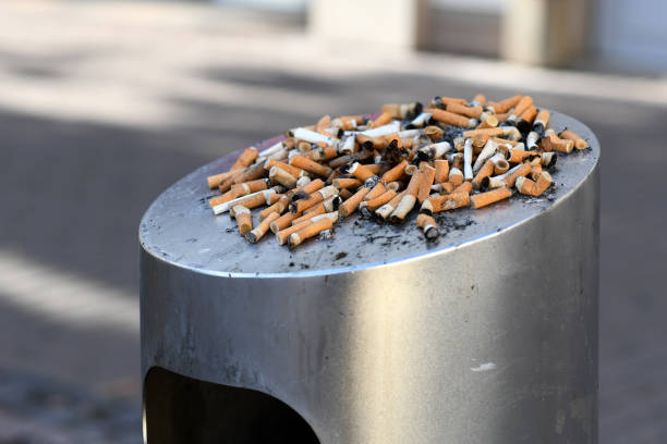 many old cigarette stubs spilling over from ashtray of overflowing public trash bin - cicca sigaretta foto e immagini stock
