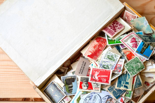 Beaucoup de vieux timbres-poste multicolores de différents pays dans la vieille boîte se trouvant sur un fond en bois - Photo