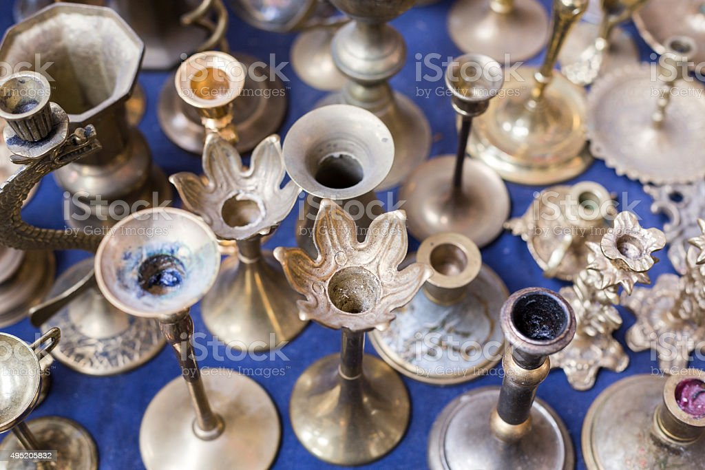 many old silver candle-stands on a flea market stock photo