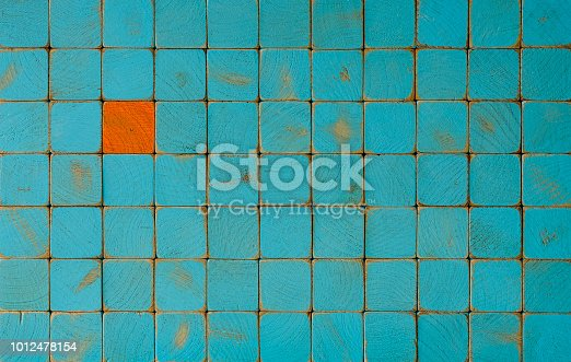 Many old turquoise weathered wooden blocks with one opposite color orange wooden block sitting among the the turquoise ones. Concept image relating to standing out from the crowd, against the grain, singled out etc.