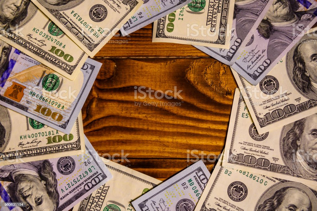 Many one hundred dollar bills on wooden table stock photo