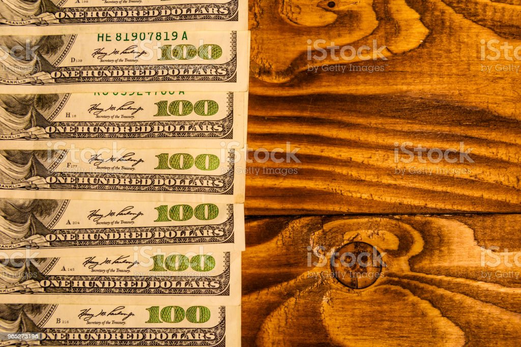 Many one hundred dollar bills on wooden table royalty-free stock photo