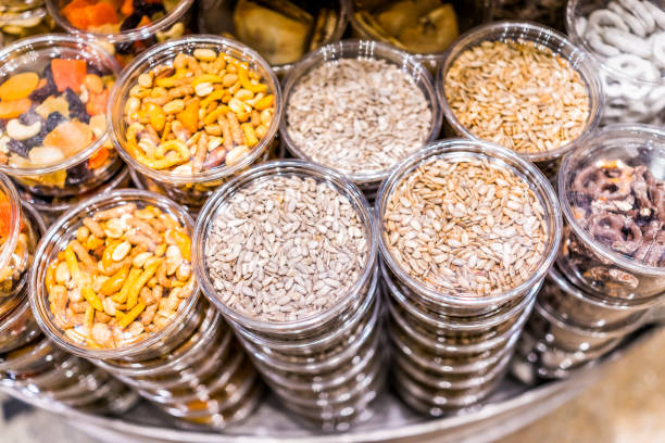 Many packaged seeds, nuts, dried fruit in plastic containers on display on store shop shelves, sunflower seeds mix, pretzels stock photo