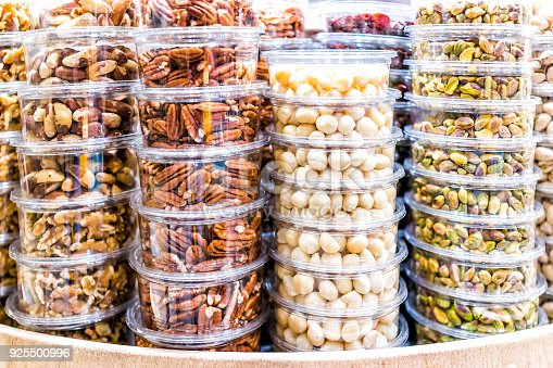 Many packaged seeds, nuts, dried in plastic containers on display on store shop shelves, macadamia, roasted, pistachios shelled, pecans, brazil, walnuts