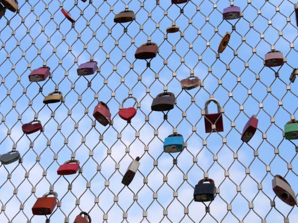 Viele Vorhängeschlösser von Liebhabern hängen an einem Brückengeländer gegen blauen Himmel am Drahtgeflecht – Foto