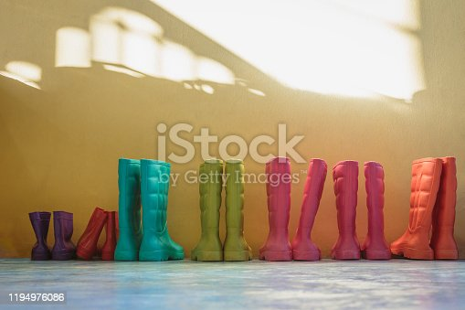 Many pairs of children's boots are placed in the room at home or kindergarten