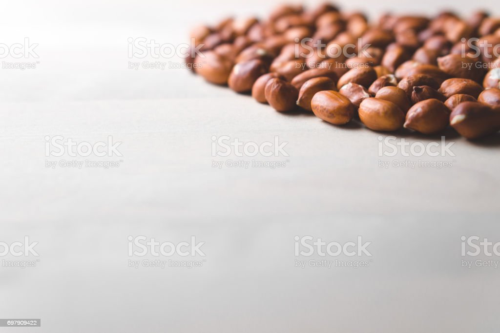 Many peanuts on wooden table. Bunch of nuts. Group of groundnuts. Free empty copy space for text. stock photo