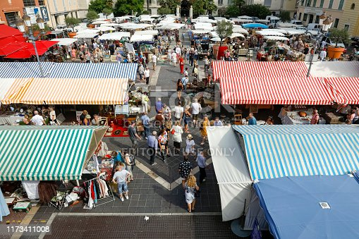 Nice, France - September 17, 2018: Many people came to the market called Cours Saleya. The canvas roof of the stalls protects the goods presented there from the sun. The city of Nice with its old town is full of historic buildings, churches and its narrow and shady streets allow you to feel the spirit of Old Nice. Contemporary architecture also emphasizes the modern character of the city. Nice is one of the most populated urban areas in France and the city is located on the French Riviera. Nice is the second largest city in the Provence-Alpes-Cote d'Azur region, and its location on the southeastern coast of France on the Mediterranean makes this place one of the most visited by tourists from all over the world.