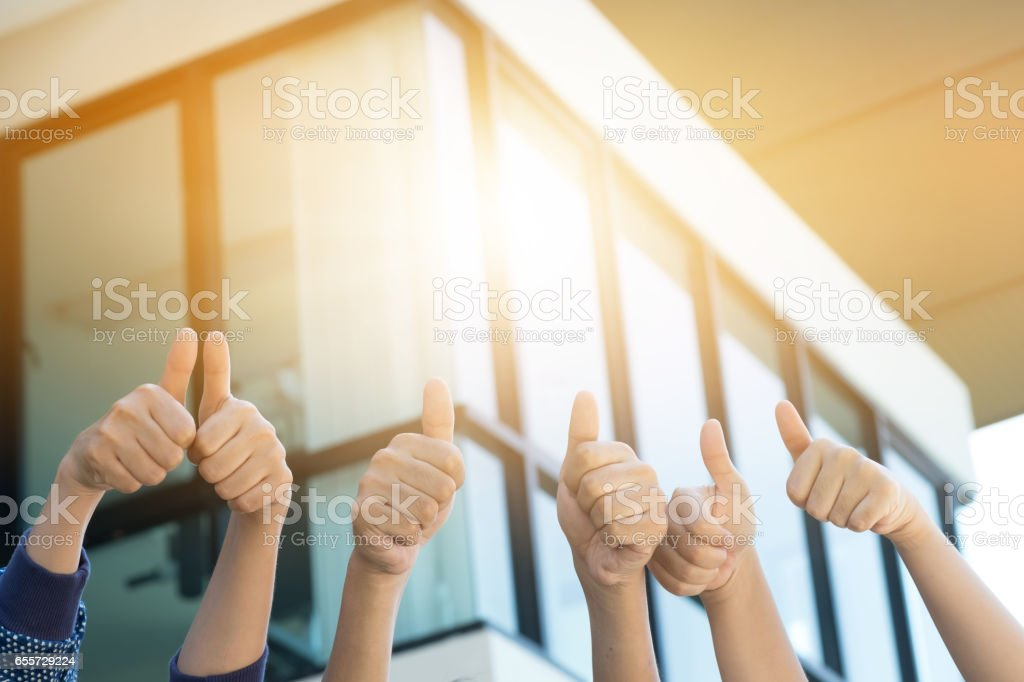 Many people congratulate a winner and holding their thumbs up stock photo