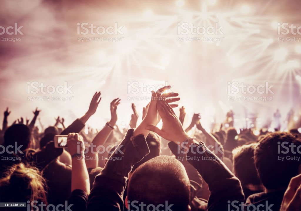 Vintage style photo of a crowd, happy people enjoying rock concert,...