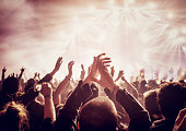 Vintage style photo of a crowd, happy people enjoying rock concert, raised up hands and clapping of pleasure, active night life concept