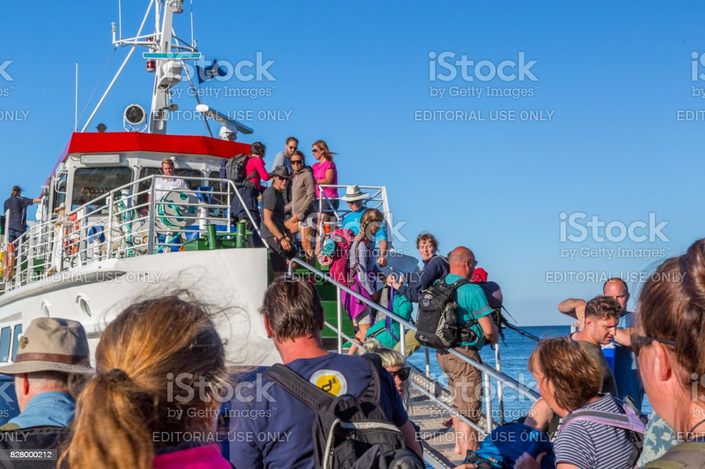 Many people entering a ship on an gangway. stock photo