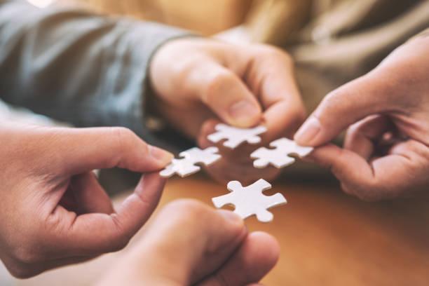 Viele Menschen halten und setzen ein Stück weißes Puzzle zusammen – Foto