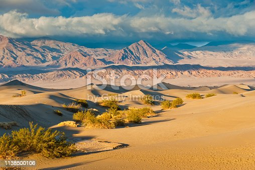 Many people identify the typical desert as a vast area covered by sand dunes. That may be true in some parts of the world but in the Mojave, less than one percent of the desert is covered with sand dunes. In order for sand dunes to exist there has to be a source of sand. Also there needs to be winds to move the sands and a place for the sand to collect. The eroded canyons and washes of Death Valley National Park in California provide plenty of sand. The wind seems to blow frequently here, especially in the springtime, and there are a few areas where the sand is trapped by geographic features such as mountains. Mesquite Flats near Stovepipe Wells is one such place. This sunset picture of the sand dunes and the Grapevine Mountains was taken after a winter storm had passed.