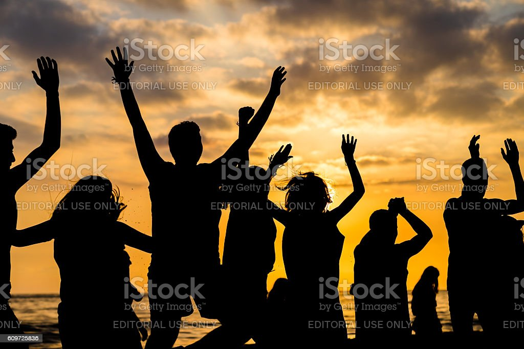 Many people jumping in sunset stock photo