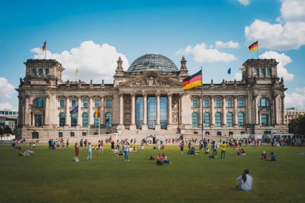 Viele Menschen auf der Wiese vor dem Reichstagsgebäude, einem berühmten Wahrzeichen an einem sonnigen Sommertag – Foto