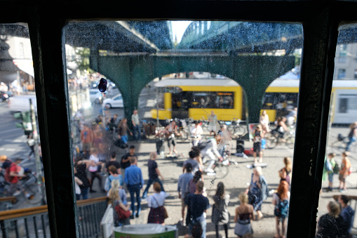 many people on street , looking through dirty window on busy street