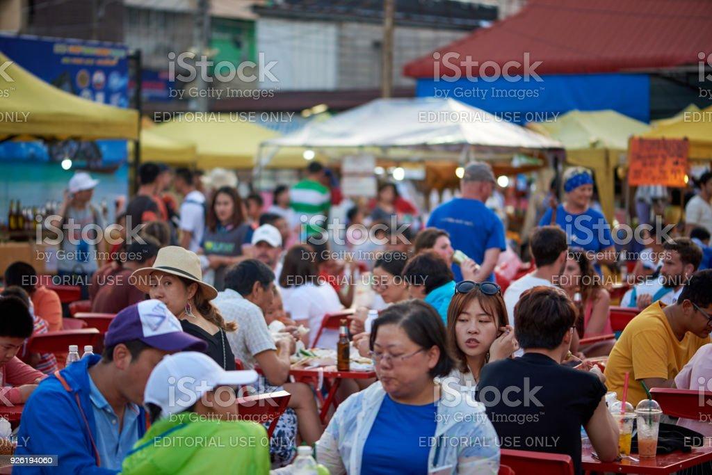 Many people sitting at tables and eating at Krabi walking street