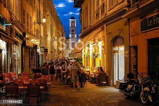 Nice, France - September 24, 2018: There are many people spending their time outdoors during the night. There are people who enjoy their time spend in nearby cafes. The city of Nice with its old town is full of historic buildings, churches and its narrow and shady streets allow you to feel the spirit of Old Nice. Contemporary architecture also emphasizes the modern character of the city. Nice is one of the most populated urban areas in France and the city is located on the French Riviera. Nice is the second largest city in the Provence-Alpes-Cote d'Azur region, and its location on the southeastern coast of France on the Mediterranean makes this place one of the most visited by tourists from all over the world.
