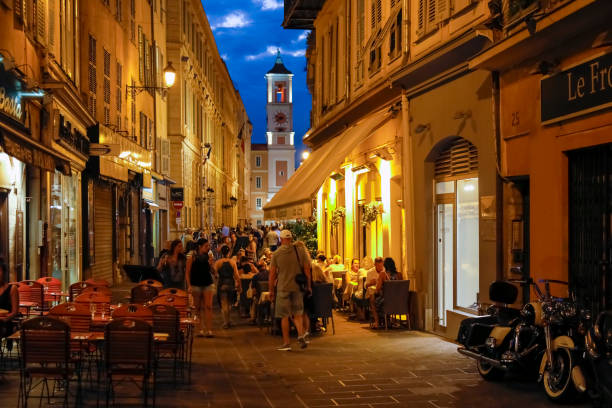 Many people spend time in outdoor cafes at night. The city of Nice is located on the French Riviera in the Provence-Alpes-Cote d'Azur region