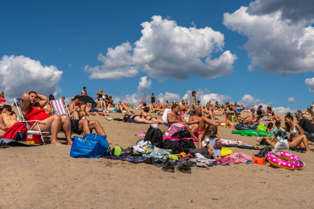 Many people sunbathing and having picnic on a beach with blue sky and clouds. stock photo