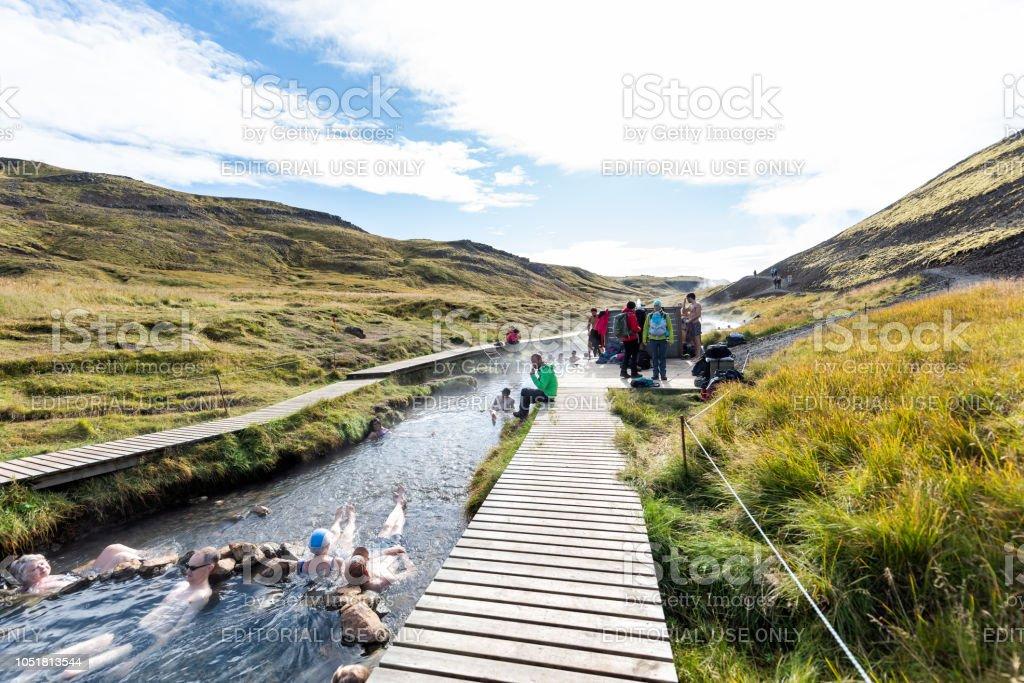 Muitas pessoas nadando, tomando banho no Hot Springs em trilha em Reykjadalur, durante o dia de Outono no sul da Islândia, círculo dourado, mudando empata - foto de acervo